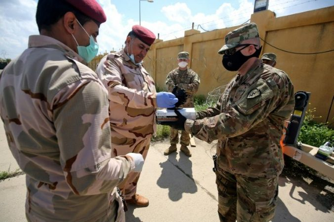 US soldier hands out masks to Iraqi soldiers in northern Iraq March